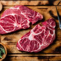 Raw marbled beef steaks on wooden cutting board. Top view